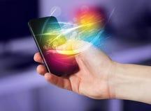 递拿着有抽象发光的线的巧妙的电话 免版税库存图片