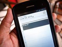递拿着有日历提示的一个智能手机 免版税库存图片