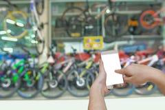 递拿着有模糊的陈列室自行车bac的流动巧妙的电话 免版税库存照片