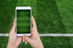 递拿着有橄榄球场屏幕的流动巧妙的电话 免版税库存图片
