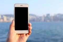 递拿着有海湾和地平线背景的大模型智能手机 免版税图库摄影