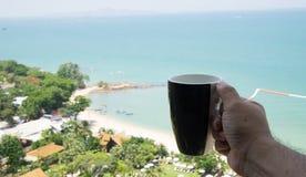 递拿着有海边的咖啡杯在背景中 免版税库存图片