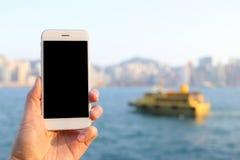 递拿着有港口和地平线背景的智能手机 免版税库存图片