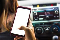 递拿着有白色屏幕的智能手机在嘲笑的汽车 免版税图库摄影