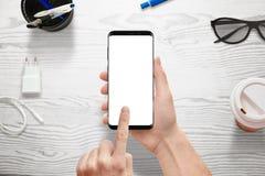 递拿着有白色屏幕的现代巧妙的电话大模型、app或者敏感网站促进的 图库摄影