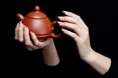 递拿着有盒盖的日本陶瓷茶壶 库存照片