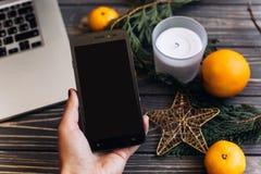 递拿着有空的屏幕的电话圣诞节季节性adve的 库存照片