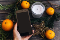 递拿着有空的屏幕的电话在圣诞节背景  库存图片