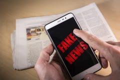 递拿着有红色假新闻词的一个智能手机在屏幕和一张报纸上在背景 图库摄影