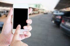 递拿着有迷离停车场的手机 库存图片