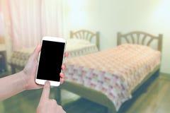 递拿着有迷离卧室的流动巧妙的电话 库存照片