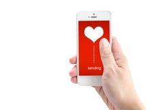 递拿着有送的词和心脏形状智能手机在scr 库存图片