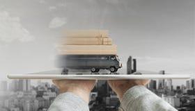 递拿着有送货卡车运载的邮包箱子的数字式片剂 网上购物、电子商务和交付概念 库存图片