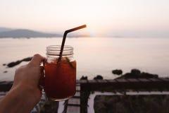 递拿着杯柠檬在热带海海滩的冰茶在太阳 库存图片