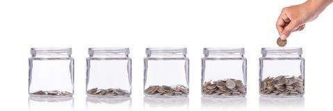 递拿着泰国硬币(泰铢)并且插入清除玻璃瓶子 stu 库存图片