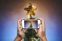 递拿着流动巧妙的电话,拍圣诞节星照片在圣诞树的与五颜六色的光 免版税图库摄影