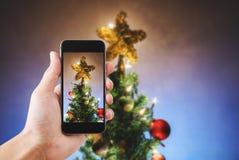 递拿着流动巧妙的电话,拍圣诞节星照片在圣诞树的与五颜六色的光 库存照片