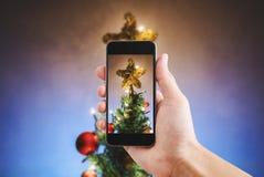 递拿着流动巧妙的电话,拍圣诞节星照片在圣诞树的与五颜六色的光 免版税库存图片