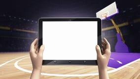 递拿着片剂空的屏幕有篮子球竞技场背景 免版税图库摄影