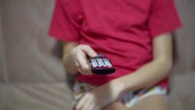 递拿着电视的女孩孩子在电视上的遥控和冲浪的节目 看电视的十几岁的女孩在客厅 影视素材