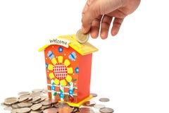 递拿着硬币并且在被隔绝的存钱罐中投入在白色backgr 免版税库存图片