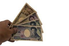 递拿着类型许多日本钞票,日元在白色背景隔绝的日本钞票 库存图片