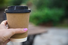 递拿着纸咖啡在自然早晨背景的 库存图片