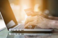 递拿着网上购物的信用卡在膝上型计算机电子商务 库存照片