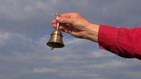 递拿着美丽的黄铜响铃和敲响它 股票视频