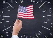 递拿着美国国旗反对海军黑板和白色烟花乱画 免版税库存照片