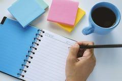 递拿着铅笔和写在日志笔记本 免版税库存图片
