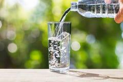 递拿着饮用水瓶倾吐的水入在木桌面的玻璃在与软的sunligh的被弄脏的绿色bokeh背景 库存照片