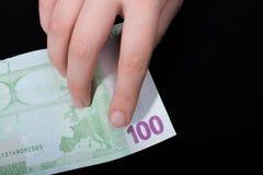 递拿着100在黑背景的欧元钞票 库存图片