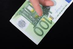 递拿着100在黑背景的欧元钞票 免版税库存图片