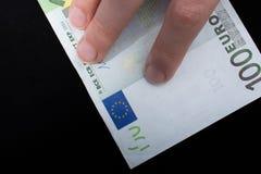 递拿着100在黑背景的欧元钞票 库存照片