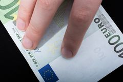 递拿着100在黑背景的欧元钞票 免版税库存照片