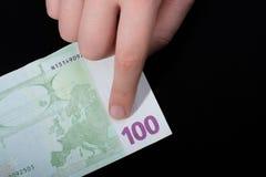 递拿着100在黑背景的欧元钞票 图库摄影