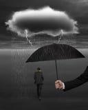 递拿着从黑暗的云彩rai的伞保护的商人 免版税库存图片