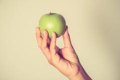 递拿着绿色苹果用有过滤器作用减速火箭的葡萄酒样式的手 库存照片