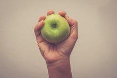 递拿着绿色苹果用有过滤器作用减速火箭的葡萄酒样式的手 库存图片
