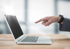 递指向膝上型计算机反对有火光的模糊的灰色办公室 免版税库存图片