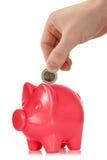 放一枚欧洲硬币入存钱罐 免版税库存图片