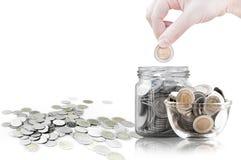 递放硬币入玻璃容器,在一个玻璃瓶子的硬币反对 免版税库存照片