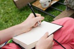 递文字对笔记薄笔记本日志,创造性的工作户外 库存图片
