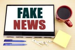 递文字文本显示假新闻的说明启发 在片剂膝上型计算机写的骗局新闻事业的企业概念 办公室pla 免版税图库摄影
