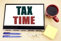 递文字文本显示税时间的说明启发 征税在片剂膝上型计算机写的财务提示的企业概念 O 免版税库存照片