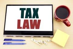 递文字文本显示税法的说明启发 征税在片剂膝上型计算机写的税收规则的企业概念 办公室p 免版税图库摄影