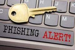 递文字文本显示Phishing戒备的说明启发 在键盘键写的欺骗警告危险的企业概念  免版税库存照片