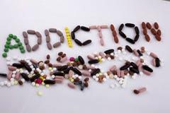 递文字文本说明启发卫生保健概念写与药片药物胶囊词毒瘾在被隔绝的白色 免版税库存照片
