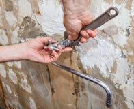 递有一把可调扳手的水管工,坚果被松开的流动的t 免版税库存图片